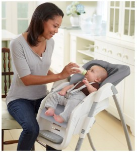 mom feeding baby in graco high chair
